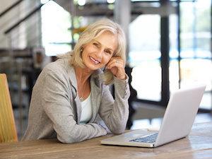 Porträt einer reifen attraktive Lady vor ihrem Laptop